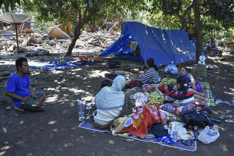 Sejumlah warga beristirahat dekat rumahnya yang roboh pascagempa di Dusun Labuan Pandan, Desa Padak Guar, Kecamatan Sambelia, Lombok Timur, NTB, Senin (20/8). Pascagempa bumi yang berkekuatan 7 Skala Richter mengguncang Lombok pada Minggu malam pukul 22.56 Wita mengakibatkan sejumlah rumah di daerah tersebut roboh dan puluhan warga mengungsi.