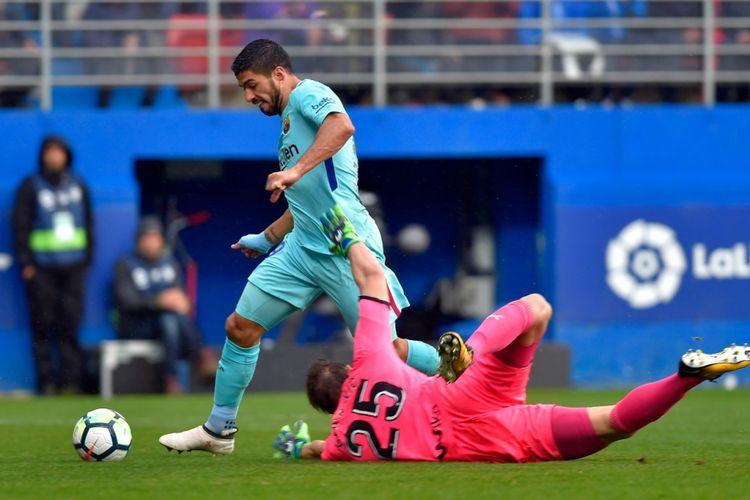 Luis Suarez Suarez mengecoh kiper Marko Dmitrovic saat Barcelona bertandang ke markas Eibar dalam pertandingan pekan ke-24 Divisi Primera La Liga Spanyol, Sabtu (17/2/2018).