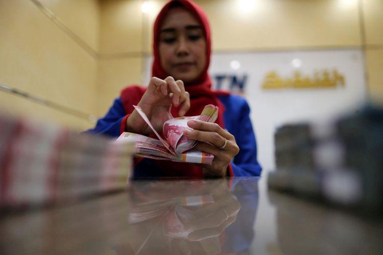 Ilustrasi. Pegawai bank menghitung uang kertas rupiah di Banking Hall BTN Syariah di kawasan Harmoni, Jakarta, Kamis (30/3/2017)  30-03-2017