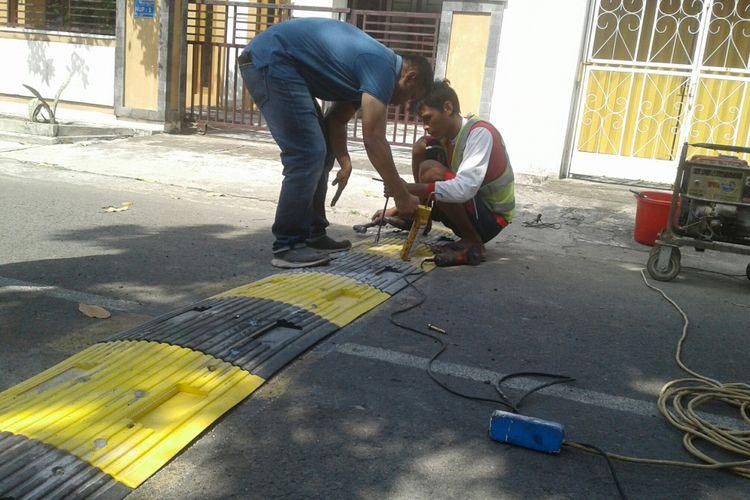 Petugas Dishub Kota Solo memasang alat pembatas kecepatan di Kampung Purwotomo, Purwosari, Laweyan, Solo, Jawa Tengah, Sabtu (26/5/2018).
