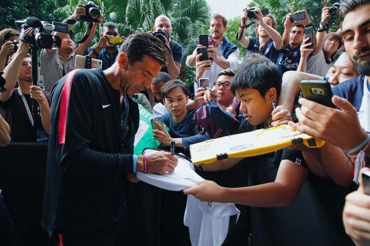 Kiper Paris Saint-Germain, Gianluigi Buffon, melayani permintaan tanda tangan dari fans saat timnya tampil di International Champions Cup di Singapura
