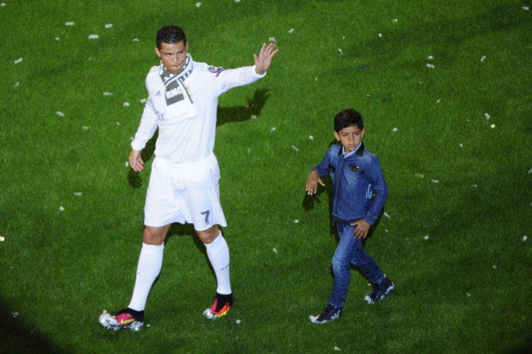 Cristiano Ronaldo membawa anaknya, Cristiano Ronaldo Jr, saat perayaan Real Madrid menjuarai final Liga Champions di Stadion Santiago Bernabeu, 29 Mei 2016.