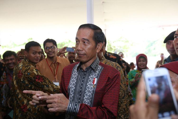 Warga menyambut Presiden Republik Indonesia Joko Widodo (Jokowi) saat tiba di acara penyerahan sertifikat tanah di Serpong, Tangerang Selatan, Banten,  Rabu  (11/10/1017). Jokowi menyerahkan 10.100 sertifikat tanah kepada warga Tangerang Raya.