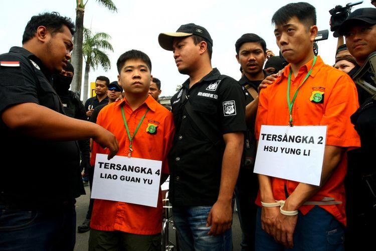 Petugas Polda Metro Jaya meminta dua tersangka penyelundup sabu 1 ton Liau Guan Yu (kedua kiri) dan Hsu Yung Li (kedua kanan) untuk memperagakan rangkaian kejahatan saat rekonstruksi di Bandara Soekarno Hatta, Tangerang, Banten, Kamis (3/8). Pada rekonstruksi tersebut polisi menghadirkan tiga tersangka hidup dan dua tersangka yang tewas yang perannya digantikan polisi dengan 16 adegan yang kesemua adegan merupakan pertemuan para tersangka setibanya di Indonesia pada 4 Juni 2017.    ANTARA FOTO/Muhammad Iqbal/ama/17