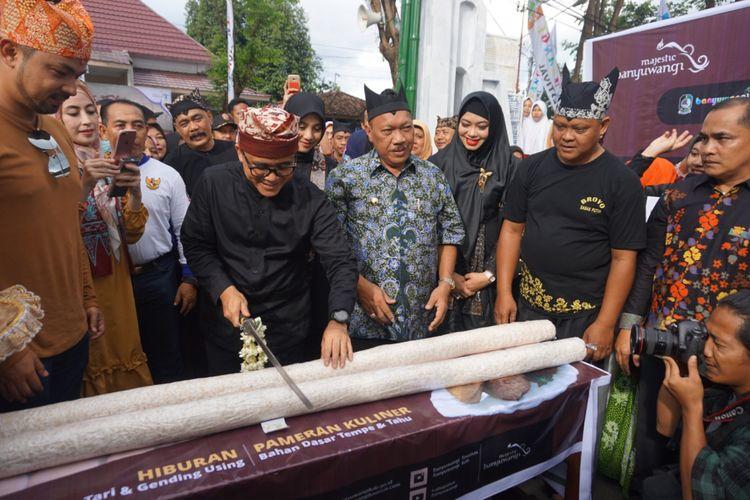 Bupati Banyuwangi Abdullah Azwar Anas sedang memotong tempe mongkleng yang memiliki panjang 2 meter pada Festival Tahu Tempe di Jalan Kalilo Banyuwangi, Jawa Timur. Festival ini digelar mulai Jumat (9/2/2018) hingga Selasa (13/2/2018), dari pukul 15.00-22.00 WIB.