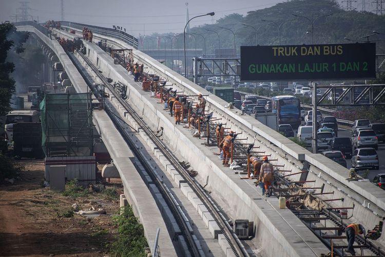 Sejumlah pekerja menyelesaikan pemasangan rel kereta ringan atau light rail transit (LRT) rute Cibubur-Cawang di Jakarta, Jumat (28/9/2018). Infrastruktur menjadi salah satu yang disuarakan Indonesia di forum IMF-World Bank Annual Meeting 2018.