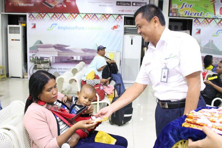Petugas Bandara El Tari Kupang, sedang membagikan cokelat kepada para penumpang pesawat, Kamis (14/2/2019)