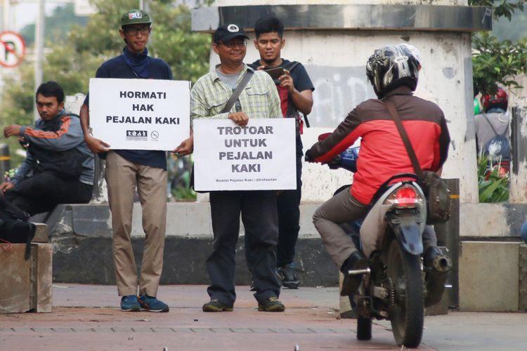 Sejumlah aktivis yang tergabung dalam Koalisi Pejalan Kaki menggelar aksi simpatik di kawasan Menteng Pulo, Jakarta, Jumat (21/7/2017). Aksi tersebut bertujuan untuk menuntut dikembalikannya fungsi trotoar bagi pejalan kaki.