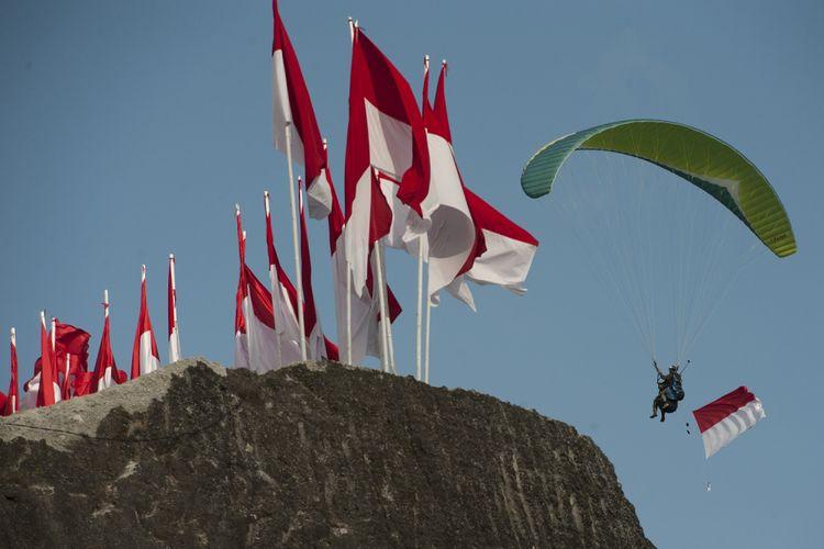 Seorang pecinta paralayang melintas di atas tebing saat pengibaran Bendera Merah Putih terpanjang di Pantai Pandawa, Badung, Bali, Senin (14/8/2017). Pengibaran Bendera Merah Putih sepanjang 800 meter tersebut untuk memperingati HUT ke-72 Proklamasi Kemerdekaan Indonesia, memperkuat nasionalisme dan sekaligus memecahkan rekor MURI. ANTARA FOTO/Nyoman Budhiana/pd/17.