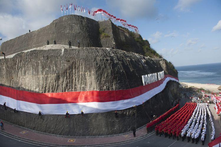 Anggota Brimob Polda Bali dan Basarnas mengibarkan Bendera Merah Putih di dinding tebing Pantai Pandawa, Badung, Bali, Senin (14/8/2017). Pengibaran Bendera Merah Putih sepanjang 800 meter tersebut untuk memperingati HUT ke-72 Proklamasi Kemerdekaan Indonesia, memperkuat nasionalisme dan sekaligus memecahkan rekor MURI. ANTARA FOTO/Nyoman Budhiana/pd/17.