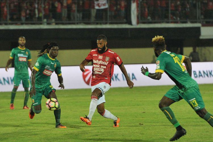 Pesepak bola Bali United Sylvano Comvalius (tengah) berebut bola dengan pesepak bola Sriwijaya FC Bio Paulin Piere (kedua kiri) dalam Pertandingan Sepak Bola Liga 1 di Stadion I Wayan Dipta, Gianyar, Bali, Senin (30/10/2017). Bali United menang atas Sriwijaya dengan skor 3-2.