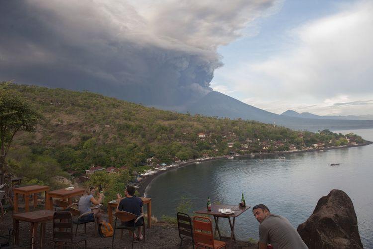 Sejumlah wisatawan menyaksikan letusan Gunung Agung dari Pantai Jemeluk, Karangasem, Bali, Minggu (26/11/2017). Pusat Vulkanologi dan Mitigasi Bencana Geologi menyatakan telah terjadi letusan freatik kedua pada pukul 17.20 Wita yang disusul dengan semburan asap dan abu vulkanis hingga ketinggian 3.000 meter.