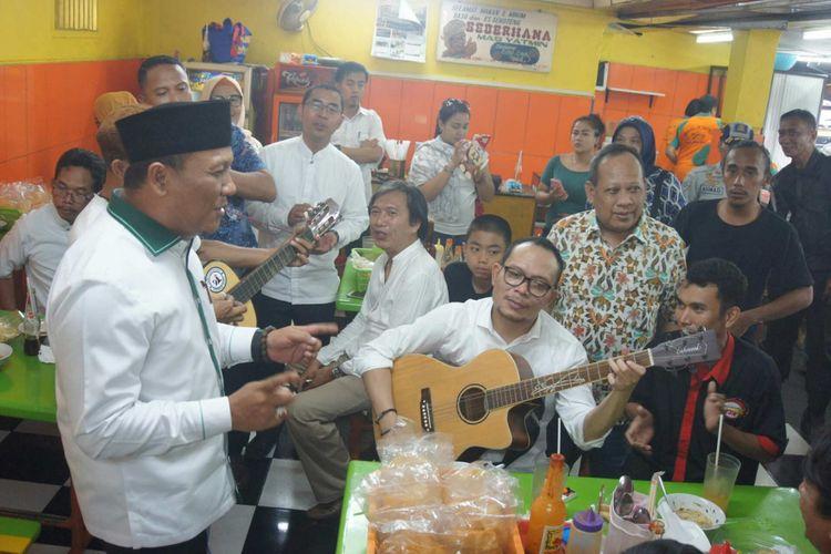 Menteri Tenaga Kerja dan Transmigrasi Hanif Dhakiri saat memetik gitar dan bernyanyi di sela menyantap bakso Yamin di Jalan Niaga, Karawang, Sabtu (21/4/2018).
