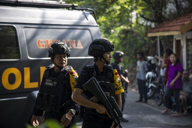 Anggota polisi berjaga di lokasi lokasi ledakan bom di gereja di Surabaya, Minggu (13/5/2018).