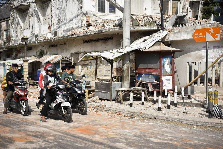 Sejumlah pengendara sepeda motor melintas dekat bangunan yang sebagian temboknya roboh akibat gempa susulan 6,2 SR di Ampenan, Mataram, NTB, Kamis (9/8). Pada Kamis (9/8/2018) pukul 13:25:32 WITA, gempa susulan dengan magnitudo 6,2 SR kembali mengguncang Lombok yang berpusat di Lombok Utara pada kedalaman 12 km getaran dirasakan di wilayah Lombok Utara,Mataram dan Lombok Tengah. ANTARA FOTO/Ahmad Subaidi/aww/18.