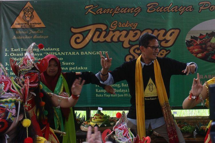 Bakal Calon Wakil Presiden Sandiaga Uno menari bersama seniman saat mengunjungi Kampung Budaya Topeng Malangan Polowijen, Malang, Jawa Timur, Rabu (12/9). Sandiaga menyatakan dukungannya terhadap upaya kreatif masyarakat Polowijen untuk melestarikan budaya sekaligus menggerakkan perekonomian melalui pasar budaya di kawasan tersebut.