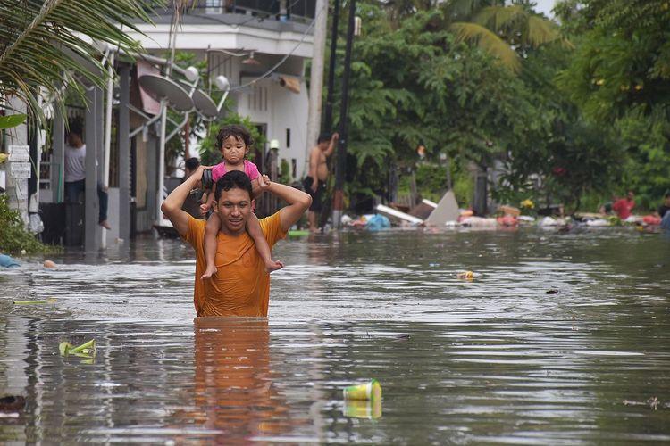 Seorang warga melintasi banjir saat mengevakuasi keluarganya di kawasan perumahan jalan Pura Demak, Denpasar, Sabtu (8/12/2018). Hujan deras yang mengguyur wilayah Bali selatan pada Sabtu dinihari menyebabkan sejumlah kawasan di Denpasar terendam banjir sehingga sejumlah warga dievakuasi. ANTARA FOTO/Adhi Prayitno/nym/hp.