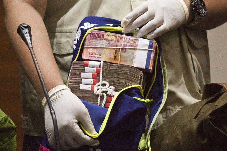 Penyidik menunjukkan barang bukti uang saat konferensi pers mengenai Operasi Tangkap Tangan (OTT) kasus korupsi pejabat Kementerian Pekerjaan Umum dan Perumahan Rakyat (PUPR) dengan pihak swasta, di Gedung KPK, Jakarta, Minggu (30/12/2018) dini hari. Dari OTT tersebut KPK menyita barang bukti uang dalam tiga pecahan mata uang sebesar 3.200 dolar AS, 23.100 dolar Singapura, dan Rp3,9 miliar, serta menangkap 20 orang terkait proyek sistem penjernihan air minum (SPAM) Ditjen Cipta Karya tahun 2018 di sejumlah daerah. ANTARA FOTO/Galih Pradipta/kye.