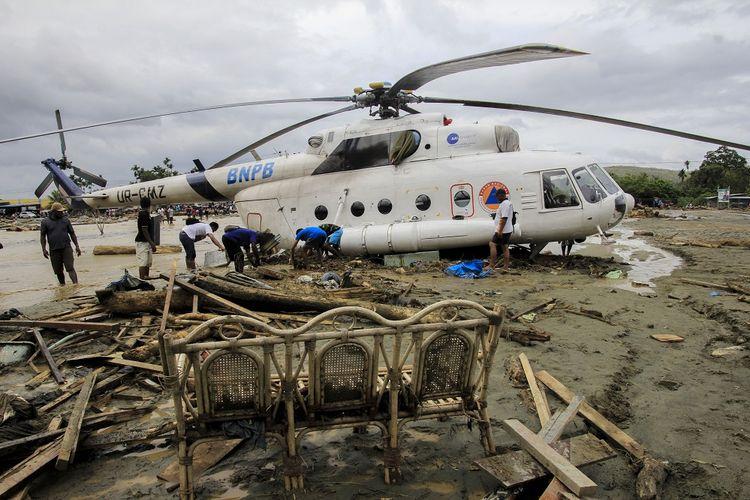 Sejumlah warga berada di dekat helikopter yang bergeser dari tempatnya akibat banjir bandang di Sentani, Kabupaten Jayapura, Papua, Minggu (17/3/2019). Berdasarkan data BNPB, banjir bandang yang terjadi pada Sabtu (16/3) tersebut mengakibatkan 42 tewas. ANTARA FOTO/Gusti Tanati/wpa/ama.