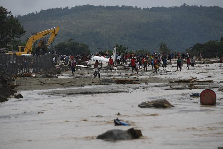 Warga mengamati sebuah pesawat yang terseret banjir bandang di Sentani, Jaya Pura, Papua, Senin (18/3/2019). Akibat banjir bandang yang melanda Sentani sejak Sabtu (16/3) lalu, sedikitnya empat ribu warga mengungsi di sejumlah posko pengungsian. ANTARA FOTO/Zabur Karuru/foc.