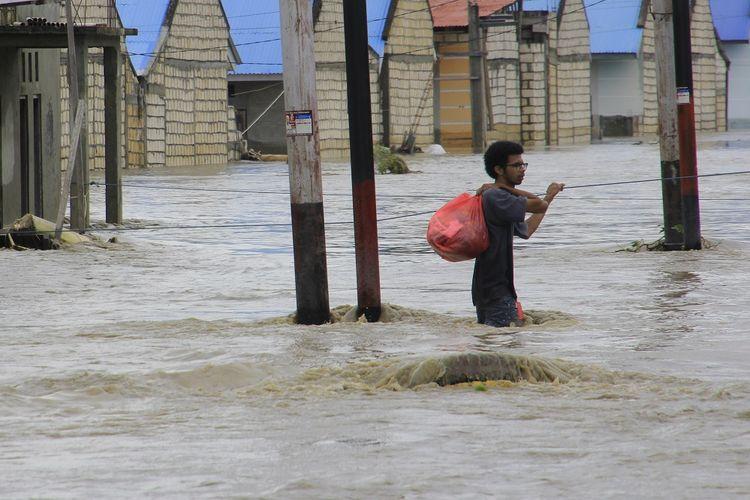 Seorang warga menyelamatkan barang berharga miliknya dari rumahnya yang terendam banjir akibat banjir bandang Sentani Jayapura, Papua, Senin (18/3/2019). Berdasarkan data BNPB tercatat sebanyak 77 orang meninggal dunia, 43 orang belum ditemukan, 74 orang luka-luka dan 4.226 orang mengungsi akibat banjir bandang yang melanda Sentani pada Sabtu (16/3). ANTARA FOTO/Gusti Tanati/ama.