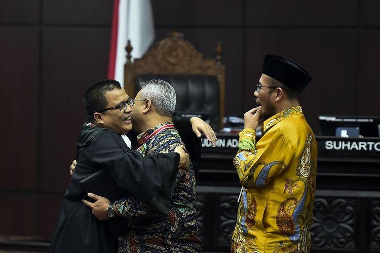 Ketua Komisi Pemilihan Umum (KPU) Arief Budiman (tengah) memeluk Tim kuasa hukum pasangan calon presiden dan calon wakil presiden nomor urut 02 Denny Indrayana (kiri) disaksikan Komisioner KPU Hasyim Asyari  (kanan) usai mengikuti sidang Perselisihan Hasil Pemilihan Umum (PHPU) presiden dan wakil presiden di Gedung Mahkamah Konstitusi, Jakarta, Jumat (21/6/2019). Sidang tersebut beragendakan mendengar keterangan saksi dan ahli dari pihak terkait yakni paslon nomor urut 01 Joko Widodo (Jokowi)-Maruf Amin. ANTARA FOTO/Galih Pradipta/hp.