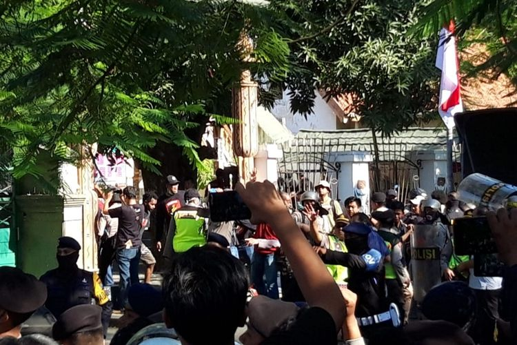 Sejumlah polisi menggunakan perisai mendobrak dan menjebol pintu pagar Asrama Papua Surabaya di Jalan Kalasan, Surabaya, Jawa Timur, Sabtu (17/8/2019).(KOMPAS.COM/GHINAN SALMAN)