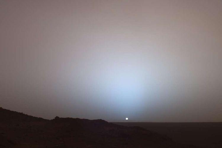 Pemandangan matahari terbenam di atas Kawah Gusev, Mars yang diambil oleh Spirit Rover NASA pada tahun 2005. Baik aureole biru dan langit merah muda terlihat.