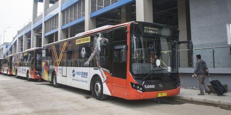 Calon penumpang berjalan di dekat bus Metrotrans saat uji coba integrasi dengan Kereta Bandara pada hari pertama di Stasiun Sudirman Baru, Jakarta, Kamis (28/12/2017). Integrasi Metrotrans dengan Kereta Bandara itu bertujuan untuk memberikan kenyamanan kepada masyarakat.