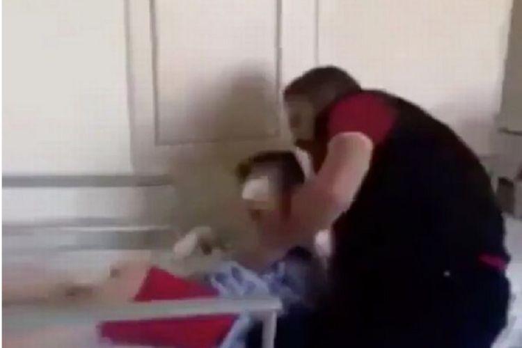 Foto yang diambil dari video ini memperlihatkan seorang pria Suriah mencoba menenangkan putranya yang terbangun dalam kondisi tak bisa melihat setelah terluka akibat sebuah serangan udara.