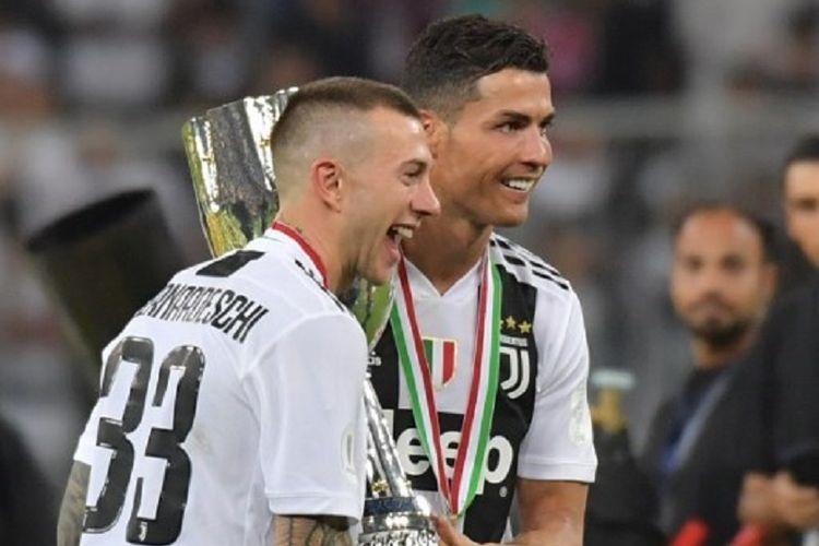 Federico Bernardeschi dan Cristiano Ronaldo mengangkat trofi Piala Super Italia seusai laga Juventus vs AC Milan di Jeddah, 16 Januari 2019.
