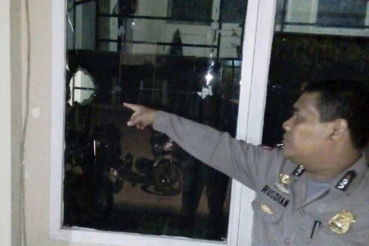 Polisi menunjukan kaca pecah di kantor Satpol PP dan WH, Lhokseumawe, Kamis (22/6/2017)