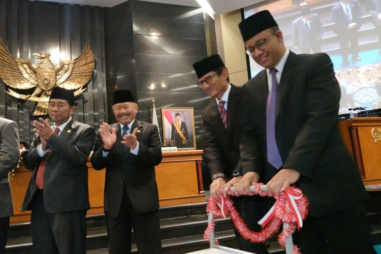 Gubernur DKI Jakarta Anies Baswedan dan Wakil Gubernur DKI Jakarta Sandiaga Uno mendorong troli berisi APBD DKI 2018 yang sudah disahkan dalam sidang paripurna di Gedung DPRD DKI Jakarta, Kamis (30/11/2017).