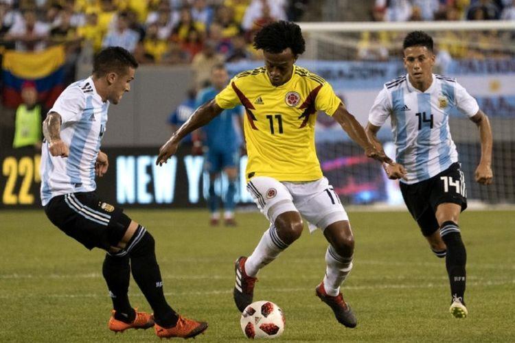Pemain asal Kolombia, Guillermo Cuadrado, mengontrol bola di tengah penjagaan bek Argentina, Fabricio Bustos dan Angel Correa, saat pertandingan persahabatan, Rabu (12/9/2018).