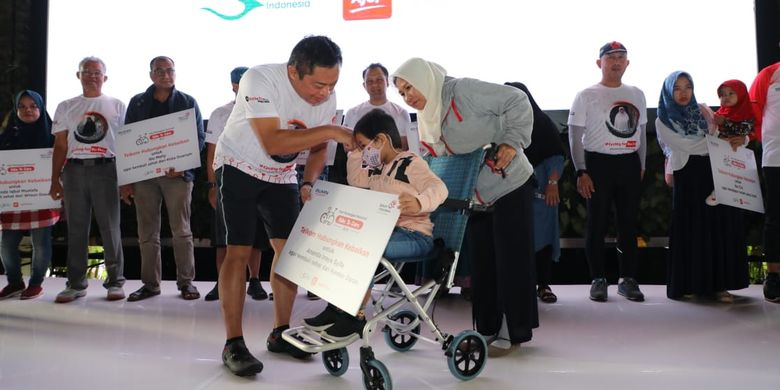 Direktur Utama Telkom Ririek Adriansyah (kiri) menyerahkan simbolis donasi kepada penderita kanker darah dalam acara Bike to Care IndiHome, di Jakarta, Rabu (4/9/2019).
