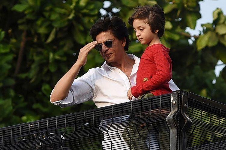 Aktor Bollywood Shah Rukh Khan dan putra bungsunya, Abram Khan, menyambut ucapan selamat Idul Fitri dari penggemarnya yang berkumpul di depan rumahnya di Mumbai, India, Rabu (5/6/2019).