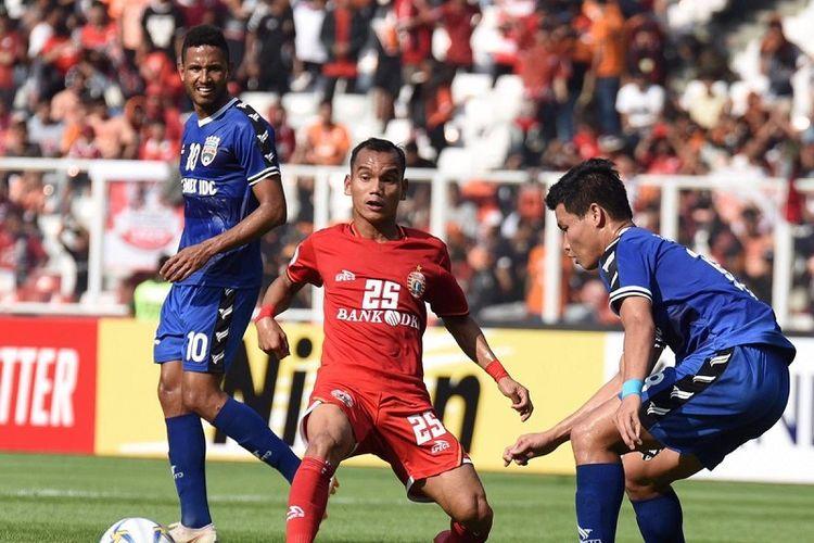 Pemain Persija Jakarta, Riko Simanjuntak dihadang pemain Becamex Binh Duong pada laga perdana penyisihan Grup G Piala AFC 2019 di Stadion Utama Gelora Bung Karno, Jakarta, Selasa (26/2/2019). Laga tersebut berakhir dengan skor 0-0.