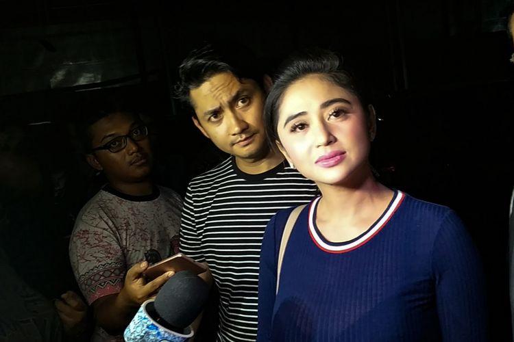 Penyanyi dangdut Dewi Perssik dan sang suami Angga Wijaya saat mendatangi Subdit Ranmor Polda Metro Jaya, Jakarta Selatan, Rabu (10/1/2018).