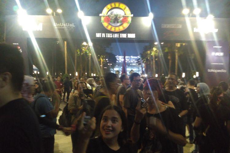 Para penonton berfoto di gapura area konser Guns N Roses sebelum memasuki area konser di Stadion Utama GBK, Senayan, Jakarta Pusat, Kamis (8/11/2018).
