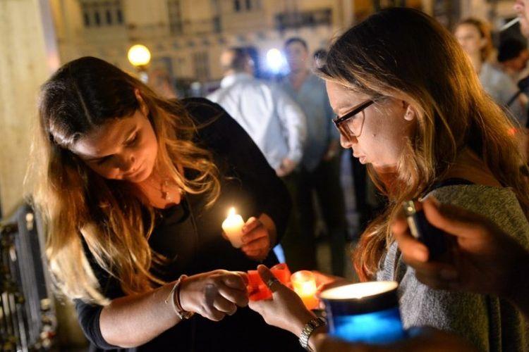 Seorang perempuan menyalakan lilin dalam doa bersama di kota Sliema, Malta untuk mengenang jurnalis Daphne Caruana Galizia yang tewas akibat bom mobil.