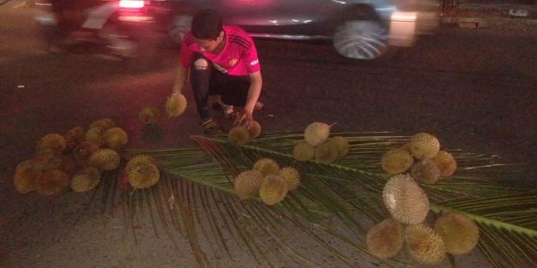 Pembeli memilih durian di Jalan Perdagangan, Kota Lhokseumawe, Aceh, Sabtu (2/3/2019) malam.