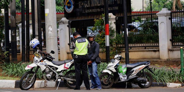 Polisi merazia pengendara sepeda motor yang melintasi trotoar di Jalan Kebon Sirih, Jakarta Pusat, Senin (17/7/2017). Pengendara sering memanfaatkan trotoar untuk memotong jalan agar bisa lebih cepat ketimbang melewati jalan raya.