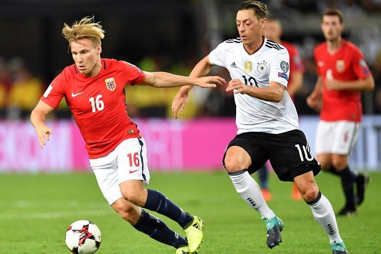 Pemain timnas Norwegia, Jonas Svensson (kiri), berebut bola dengan gelandang Jerman, Mezut Oezil, dalam pertandingan kualifikasi Piala Dunia 2018 di Stuttgart. 4 September 2017.