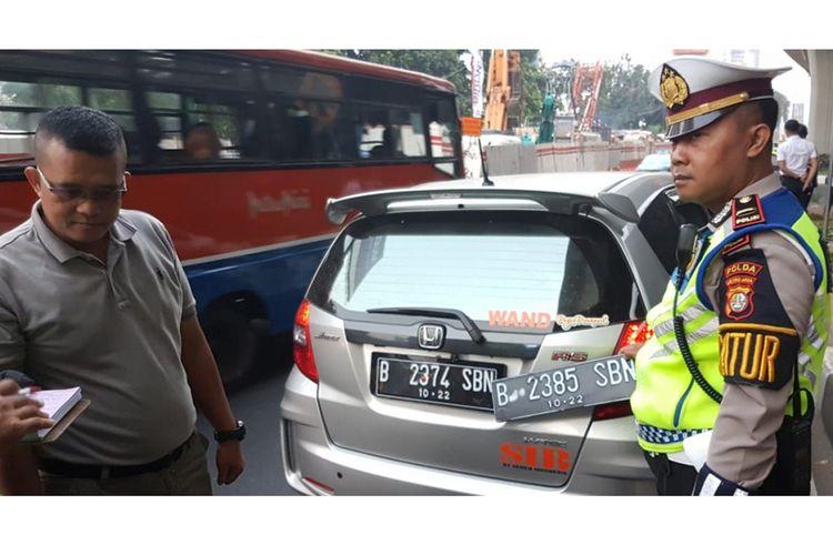 Pengemudi Honda Jazz bernama Wanda ditilang polisi karena kedapatan memiliki pelat ganda untuk menghindari aturan pembatasan kendaraan berdasarkan nomor pelat ganjil dan genap di Jalan Gatot Subroto, simpang Pancoran, Jakarta Selatan, Rabu (1/8/2018). Petugas kepolisian mulai memberlakukan penindakan berupa tilang terhadap pengendara mobil yang melanggar di kawasan perluasan sistem ganjil-genap.