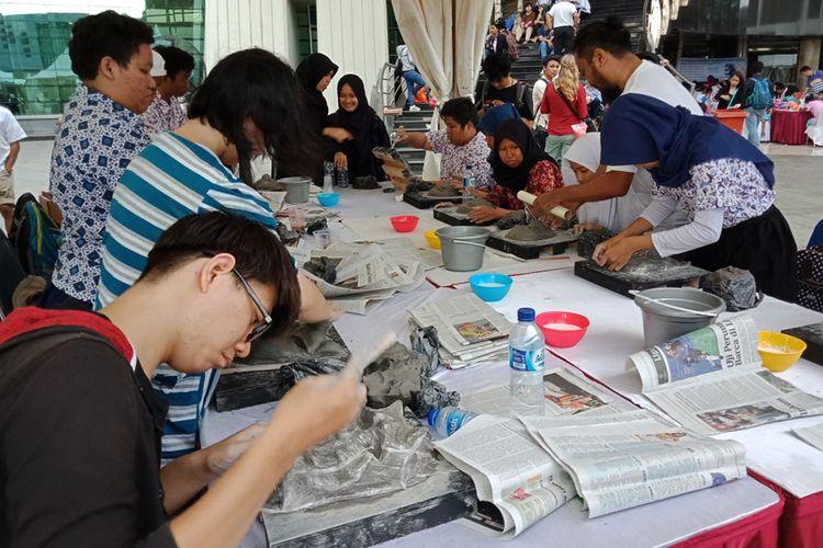 Membuat topeng kertas, salah satu kegiatan dalam acara Perempuan Disabilitas Mengubah Dunia di Taman Ismail Marzuki, Cikini, Jakarta Pusat, Kamis (8/3/2018). Dalam acara yang digelar bertepatan dengan Hari Perempuan Internasional tersebut, para penyandang disabilitas bukan hanya mempersiapkan dan menjalankan acara namun juga melakukan lomba-lomba dan aktivitas lain seperti workshop tata rias, membuat topeng, melukis, dan lainnya.