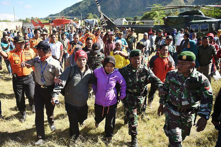 Petugas membantu pendaki Gunung Rinjani yang sempat terjebak longsor akibat gempa bumi, Suharti (tengah), setelah berhasil dievakuasi dan tiba di Lapangan Sembalun Lawang, Lombok Timur, NTB, Selasa (31/7/2018). Tiga orang pendaki yang terjebak akibat gempa berhasil dievakuasi menggunakan helikopter.