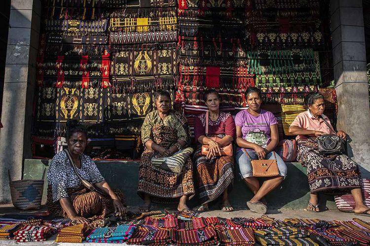 Pengrajin menunjukkan motif kain tenun ikat kepada calon pembeli di Pasar Alok, Maumere, Sikka, Nusa Tenggara Timur (NTT), Selasa (31/7/2018). Di Pasar Alok, setiap Selasa mulai pukul 06.0013.00 Wita merupakan hari khusus bagi perajin seantero Kabupaten Sikka dan daerah lainnya untuk menjual kain tenun ikat hasil kerajinan tangan yang dibuat dengan mesin tenun tradisonal.