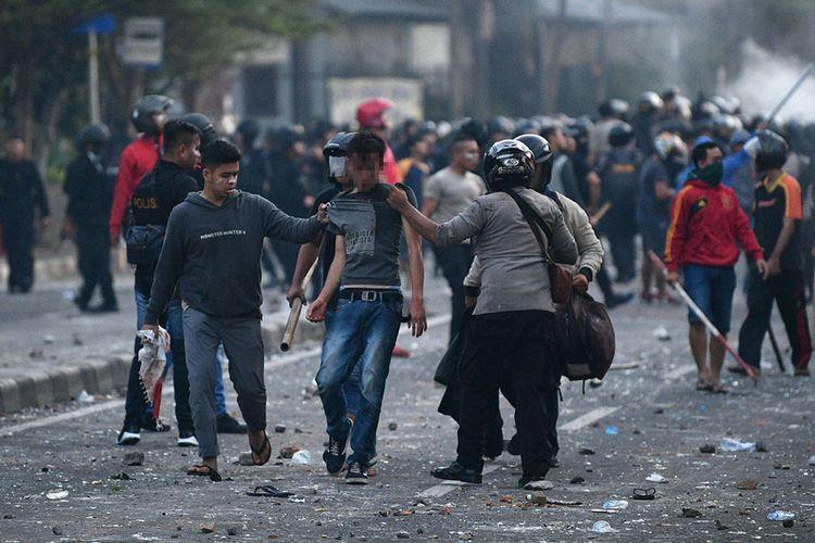 Polisi mengamankan pendemo yang rusuh di Jalan KS Tubun, Jakarta, Rabu (22/5/2019). Bentok terjadi setelah massa dipukul mundur dari kericuhan di Tanah Abang, Jakarta Pusat, Selasa (21/5/2019) malam.
