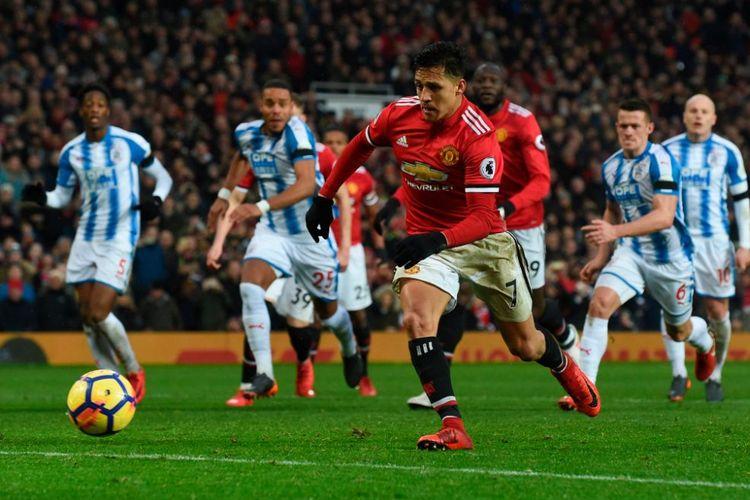 Alexis Sanchez mengeksekusi tendangan penalti saat Manchester United berhadapan dengan Huddersfield Town pada laga Premier League di Stadion Old Trafford, Sabtu (3/2/2018).