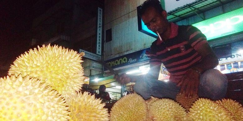 Pedagang memilihkan durian untuk pembeli di Jalan Perdagangan, Kota Lhokseumawe, Aceh, Sabtu (2/3/2019) malam.